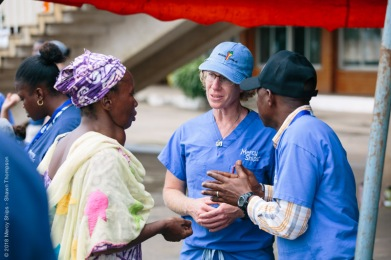 Missy Brown, OR Manager, talking to a potential patient at the mass screening at Palais du Peuple.