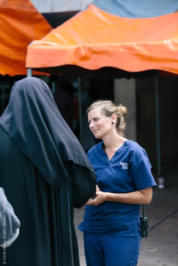 Mirjam Hamer, Screening Nurse, talking to a potential patient at the mass screening at Palais du Peuple.